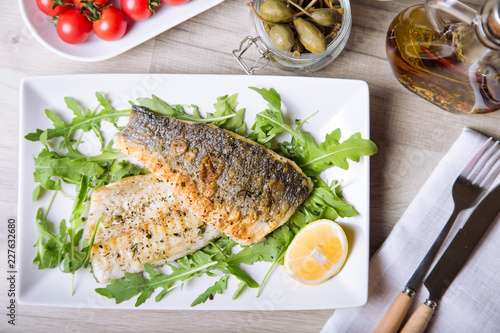 Valokuva Grilled seabass fillet with arugula, lemon, tomatoes and capers