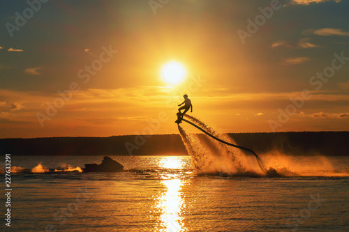 Tuinposter Water Motor sporten Silhouette of a fly board rider over a river against the setting sun.