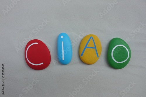 Photo  Ciao, italian greet word composed sith colored stones over white sand