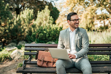 Happy Young Business Man Sitting On The Bench With Laptop.