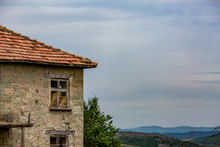 Old Abandoned Cracked Granite Stone House With Red Roof Tiles Turned Into Barn Stands Under The High Contrast Spring Sky Of Rhodope Mountains, Bulgaria. Hay Stacks Could Be Seen Through The Window
