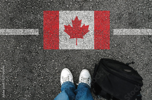 a man with a shoes and backpack is standing on asphalt nex to flag of Canada and Wallpaper Mural
