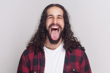 Crazy Handsome Man With Beard And Black Long Curly Hair In Casual Style, Checkered Red Shirt Standing, Open Big Mouth, Tongue Out And Looking At Camera. Indoor Studio Shot, Isolated On Grey Background