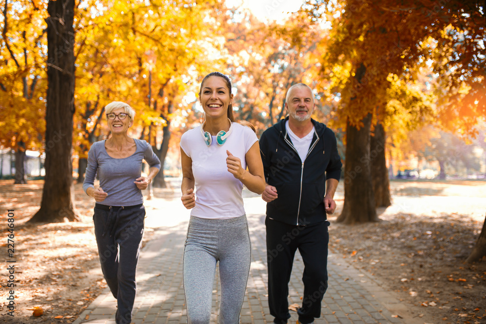 Fototapeta Senior man and woman and young female instructor  workout on fresh air. Outdoor activities, healthy lifestyle, strong bodies, fit figures. Stylish, modern sportswear. Different generations