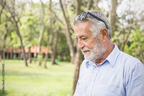 Photo  Portrait of sad senior caucasian old man thinking in the park outdoors with copy space