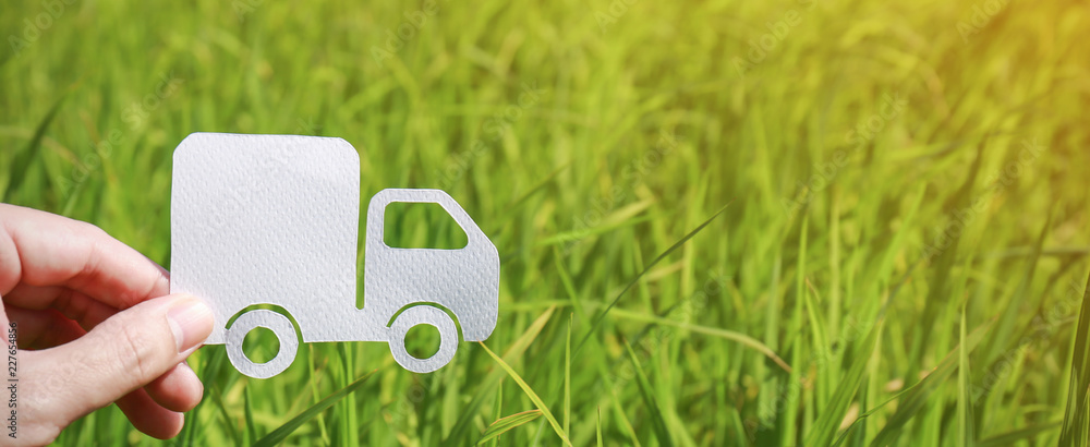 Fototapeta Paper cut of truck on green grass background, earth day concept with copy space, spring time, background silhouette delivery e-commerce transport save energy concept and banner