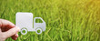 Paper cut of truck on green grass background, earth day concept with copy space, spring time, background silhouette delivery e-commerce transport save energy concept and banner