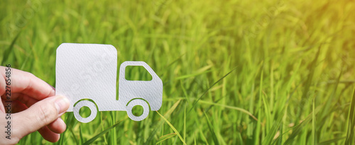 Paper cut of truck on green grass background, earth day concept with copy space, spring time, background silhouette delivery e-commerce transport save energy concept and banner - fototapety na wymiar