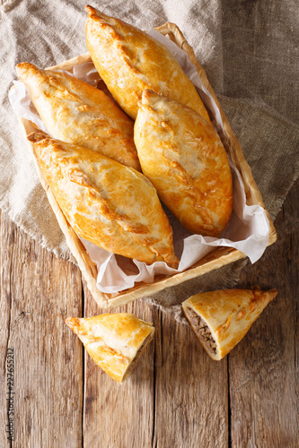 Pastry stuffed with minced meat and onion on rustic background. Karaite kibinai Lithuanian national dish close-up. Vertical top view