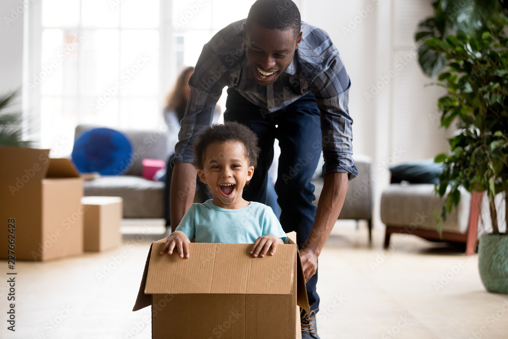 Fototapety, obrazy: Black family in living room have a fun spend time at new home. African adorable playful laughing boy sitting at cardboard box, father rolling him playing together. New property and relocation concept