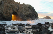 Orange Sunset Streams Through Keyhole Arch Rock Formation In Big Sur