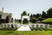 Outdoor Wedding Ceremony. Welcome Plate Decorated With Fresh Flowers And Wedding Chuppa