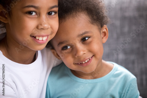 Close up portrait of beautiful adorable black African siblings toddler brother and preschool sister embracing sitting on couch together smiling looking at camera Canvas Print