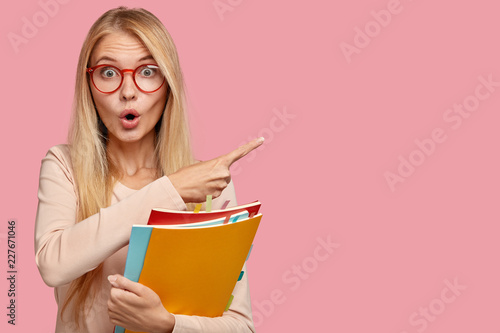 Fototapeta Photo of surprised teacher indicates aside with index finger, has light straight hair, keeps mouth opened with amazement, carries textbooks, isolated on pink background