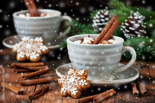 Mugs with hot chocolate  and gingerbread cookies on wooden table