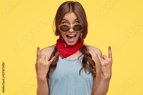 Foto  Headshot of provocative cool female hipster shows rock n roll hand gesture, exclaims something loudly, wears fashionable bandana, trendy sunglasses, poses against yellow background