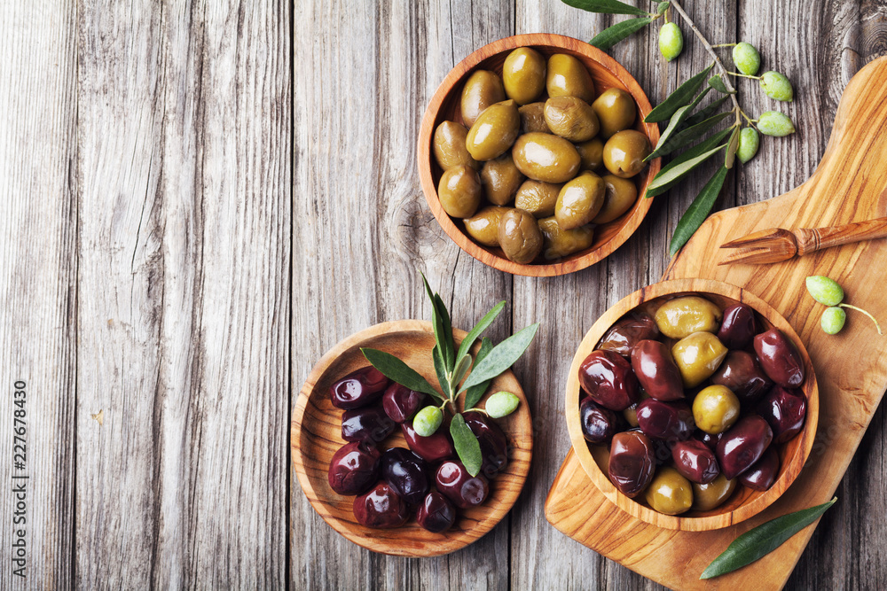 Fototapety, obrazy: Pickled olives served in bowls from olive wood on rustic kitchen table top view.