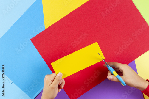 Vászonkép Kid's hands cutting colored paper with scissors