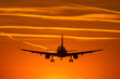 canvas print picture - Airplane prepare for landing at sunset with beautiful red sky in background