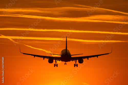 Tuinposter Airplane prepare for landing at sunset with beautiful red sky in background
