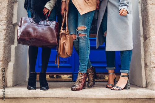 Three women wearing stylish shoes and accessories outdoors. Autumn fashion concept. Ladies holding female handbags