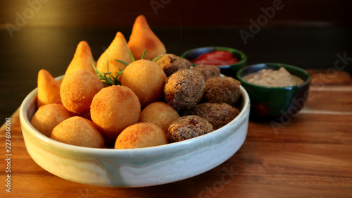 Traditional Brazilian snacks coxinha and quibe on wooden dark background. Selective focus.