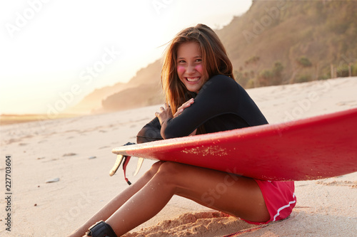 Outdoor shot of happy slim young woman with slender legs, satisfied to win surfing contest, wears casual clothes, sits on sandy beach with cliff in background. Peaceful atmosphere for good rest