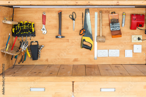 Obraz Wooden workbench at workshop. Lot of different tools for diy and repair works. Wood desk for product display. Copyspace. Labour day - fototapety do salonu