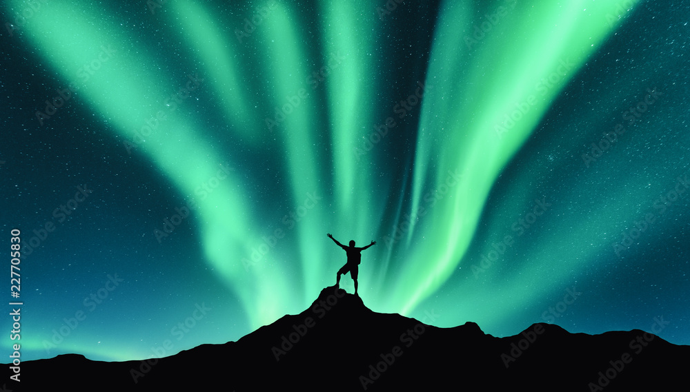 Fototapety, obrazy: Northern lights and silhouette of standing man with raised up arms on the mountain in Norway. Aurora borealis and happy man. Sky with stars and green polar lights. Night landscape with aurora. Concept