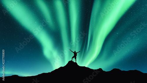 Northern lights and silhouette of standing man with raised up arms on the mountain in Norway. Aurora borealis and happy man. Sky with stars and green polar lights. Night landscape with aurora. Concept