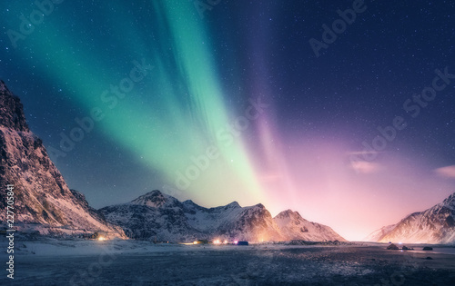 Foto auf Gartenposter Nordlicht Green and purple aurora borealis over snowy mountains. Northern lights in Lofoten islands, Norway. Starry sky with polar lights. Night winter landscape with aurora, high rocks, beach. Travel. Scenery