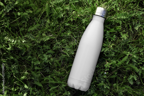 Fotografering Stainless thermos water bottle isolated on green grass outdoor