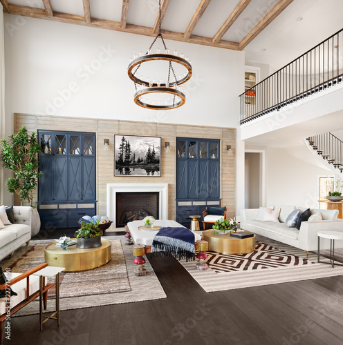 Photo Beautiful Spacious Living Room in Luxury Home with Loft, Elegant Chandelier, and Hint of Spiral Staircase