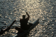 Silhouette Of A Man Paddling An Outrigger In The Ocean.