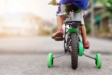 Learning To Ride A Bike Concept, The Little Boy Is Practicing Cycling A Bicycle With The Training Wheels On The Road.