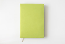 Top View Of Green Cover Notebook On White Desk Background With Copy Space