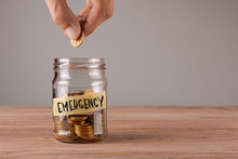 Emergency. Glass Jar With Coins And An Inscription Emergency. Man Holds  Coin In His Hand