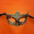 Leinwanddruck Bild - Halloween holiday minimal top view image of venetian elegant mask over orange wooden background.