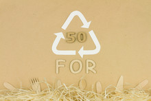 "Wooden Disposable Tableware: Forks, Spoons And Knifes Lying On Brown Background With Recycle / Reuse Symbol With Recycling Code 50 ""FOR"". Environment Issue / Care, Recycle / Reuse, Safe Planet Concept"
