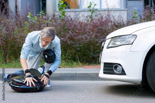 Deurstickers Cubaanse oldtimers Car accident concept. Young student male man sitting on road with knee and hand protection with eco electric unicycle and taken injury in car accident with white gasoline diesel car. Safe road concept