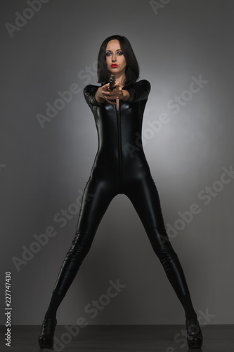 Fotografija woman in latex suit on a dark background with gun