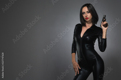 Obraz na plátně woman in latex suit on a dark background with gun
