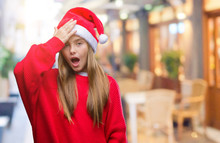 Young Beautiful Girl Wearing Christmas Hat Over Isolated Background Surprised With Hand On Head For Mistake, Remember Error. Forgot, Bad Memory Concept.