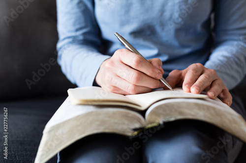 Fotografia  Bible Study - Woman Taking Notes as She Reads from an Open Bible