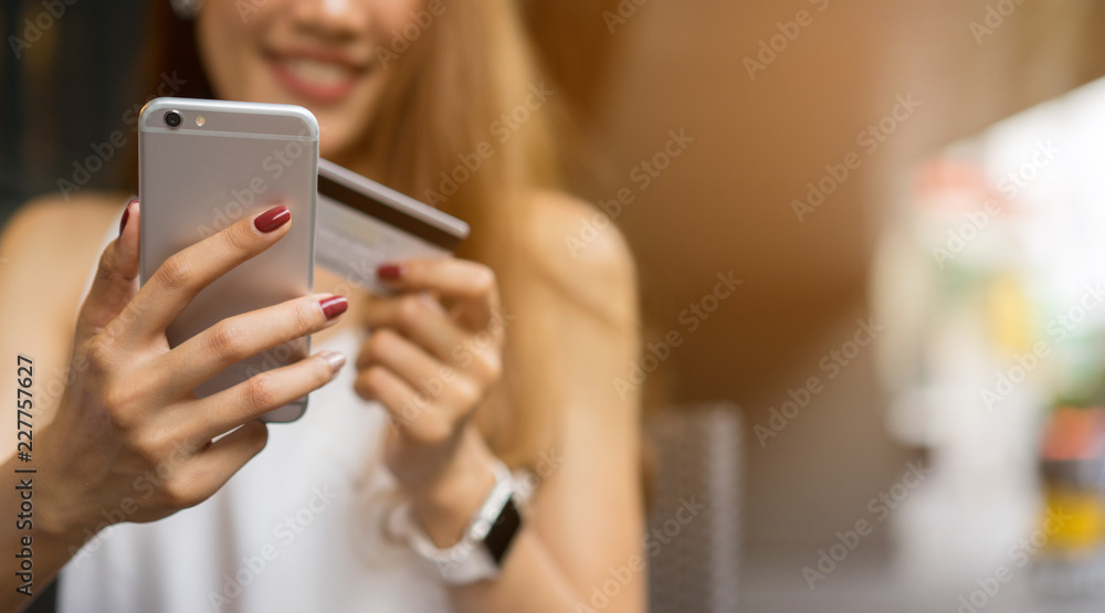 Fototapeta close up asian business woman holding smartphone with credit card for pay online shopping e-commerce concept