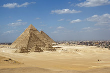 Great Pyramids Of Giza Set Against A Bright Blue Sky And Golden Yellow Desert Sands But With The Encroaching City Of Cairo In The Background