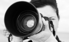 Woman With Digital Photo Camera Aimed At You. Monochrome Image