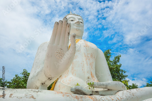 Tuinposter Boeddha The Buddha raised his hands under blue sky and clouds
