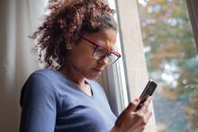 Sad Black Woman Near Window Reading Phone Message