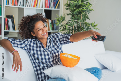 Afro woman sitting at home with remote control watching tv Fototapeta